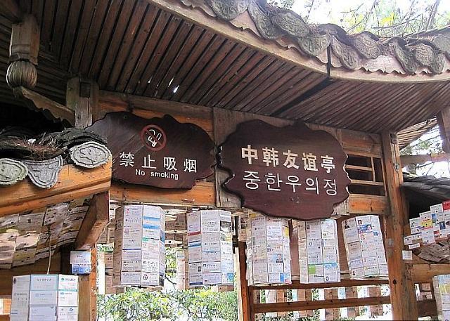 """中韩友谊亭里感受两国友好 位于袁家界景区的""""中韩友谊亭""""由土生土长的张家界人创立,是中国也是世界自然遗产中唯一以韩国名片为载体的友谊亭。友谊亭外观是一座土家族风格的小木屋,木屋中出售各种韩国零食、饮料。韩国游客到访这里时,纷纷主动留下名片给小卖店主人,后来便将名片张贴在小木屋的板壁、木柱上,时间久了,名片越积越多,现在已经超过上百万张。很多韩国游客在这里合影,并热情地招呼中国游客一起品尝马格利(韩国米酒),一张张小小的名片,见证了中韩两国的友好和交流。 在张家界景区内的宾馆、饭店、"""