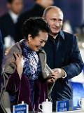 .Putin wraps shawl around Chinese first lady Peng .