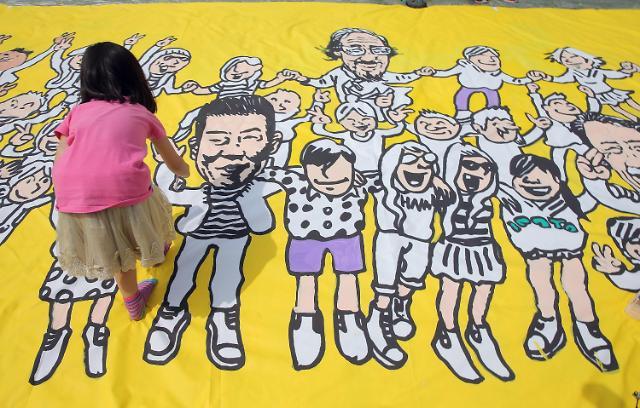 """17日,众多韩国青少年与志愿者在首尔广场一道通过绘画纪念""""光州事件""""中的遇难者。1980年5月18日至27日,韩国光州市爆发了一次由市民自发的民主运动。当时掌握军权的全斗焕将军下令武力镇压这次运动,造成大量平民和学生死亡和受伤。"""