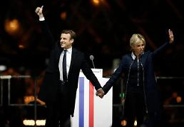.[GLOBAL PHOTO] French President-elect Emmanuel Macron holds hands with his wife.