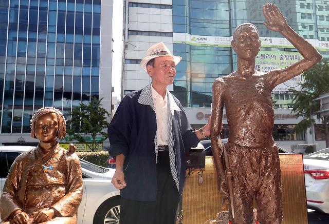 站在慰安妇少女像和强制征用铜像之间的韩国老人