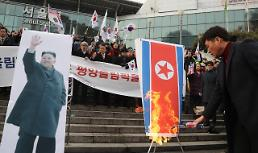 .Conservative activists torch N. Korean flag and leaders portrait.