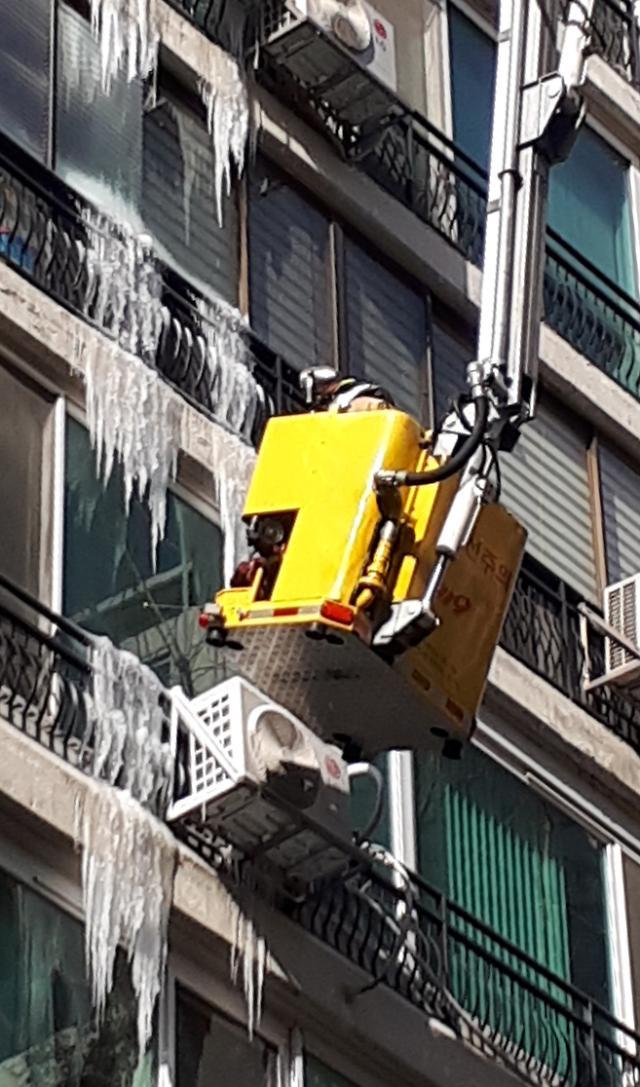 公寓楼冰柱危及行人 消防队员除冰保安全