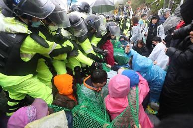 .Riot police crush sit-in to renovate barracks at U.S. missile base.