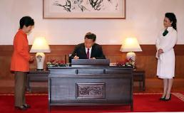 .<习近平访韩—首脑会晤>习近平在青瓦台来宾签名簿上签名.