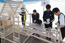 .[PHOTO] School students try building model house.