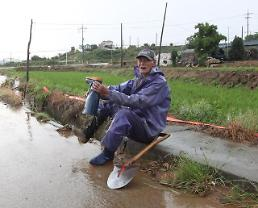 .[PHOTO] Farmer delighted by timely rain.