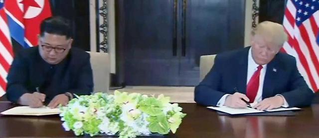 金正恩特朗普在协议书上签字