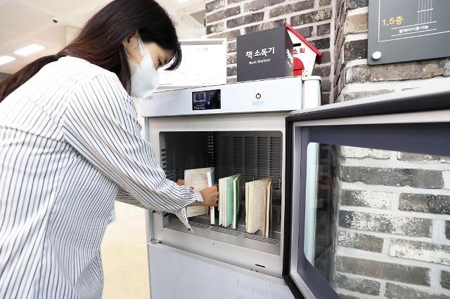 首尔江南区厅图书馆给图书消毒
