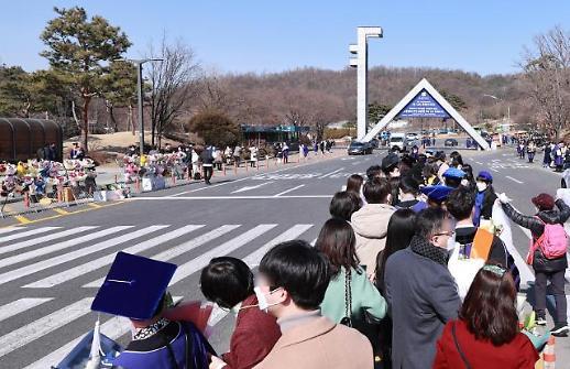 韩首尔大校门前毕业生排队拍照留念