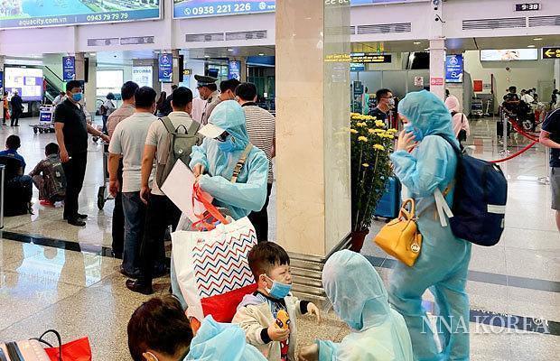 탄손냐트 국제공항에서 방호복을 입는 승객