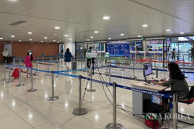 도착한 사람의 체온을 재는 노이바이 국제공항 직원