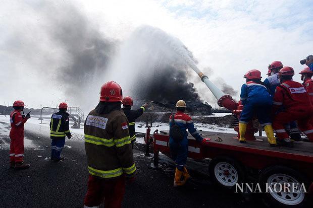 발롱강 정유소에서 발생한 화재를 진압하는 소방관
